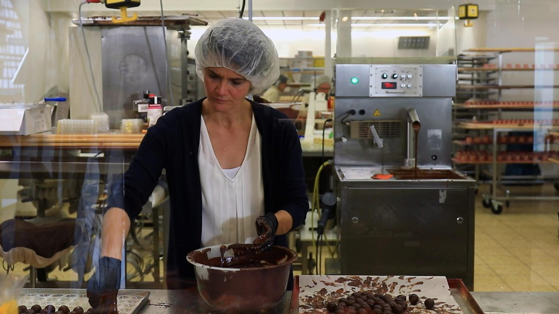 Andrea Matt trägt ein Haarnetz und überzieht Pralinen mit Schokolade.