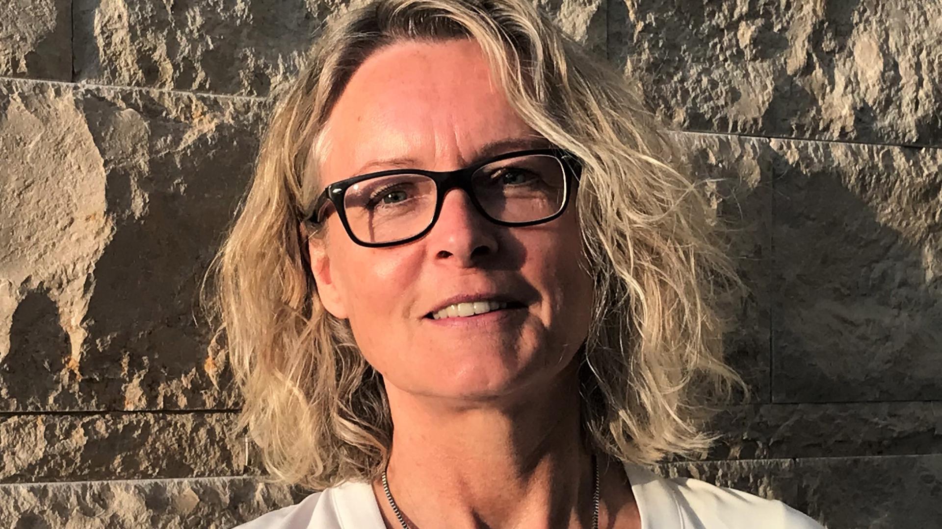 Karin Eyrer hat blonde Haare und trägt eine schwarze Brille. Sie steht vor einer Steinwand.