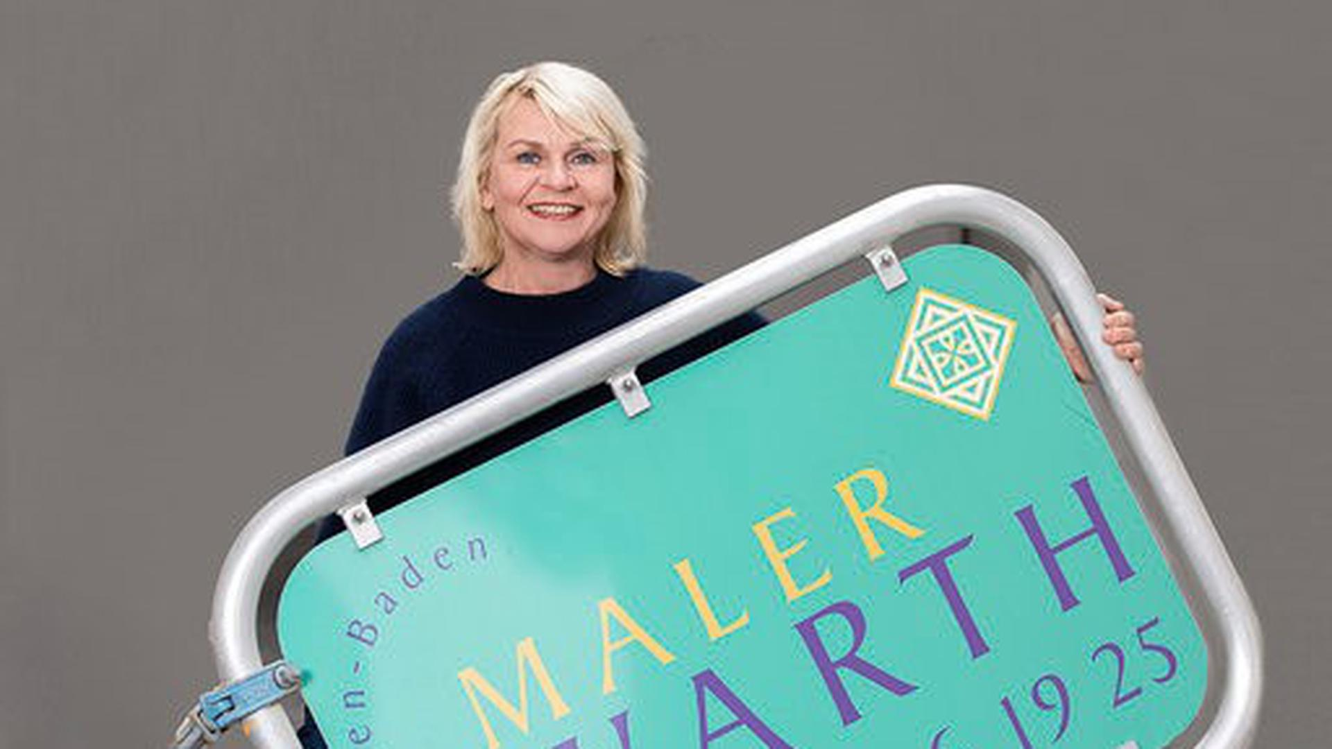 Karin Hirschböck hält ein Schild ihrer Firma hoch.
