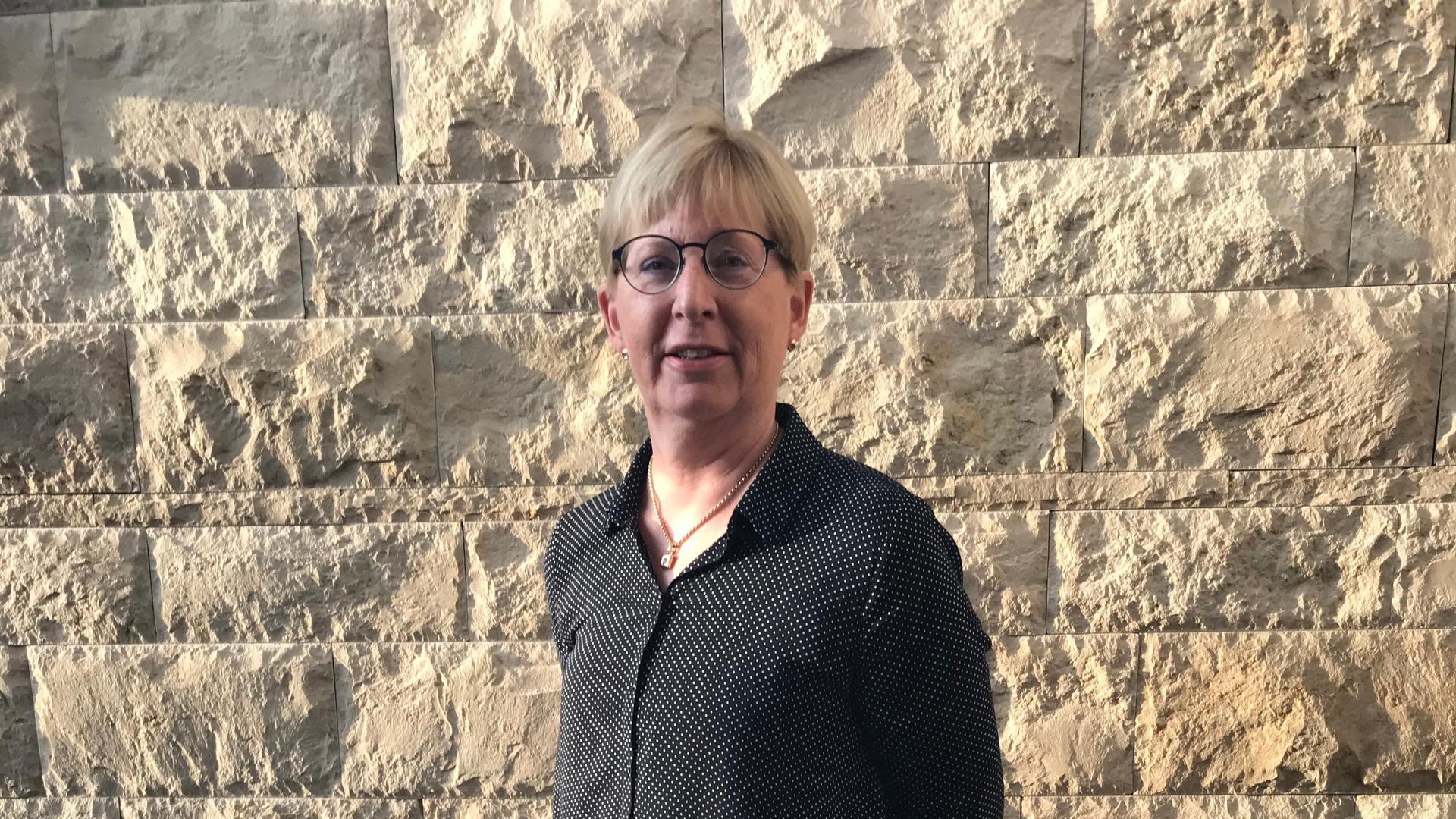 Ulrike Linder hat blonde Haare und trägt eine schwarze Brille. Sie steht vor einer Steinmauer.