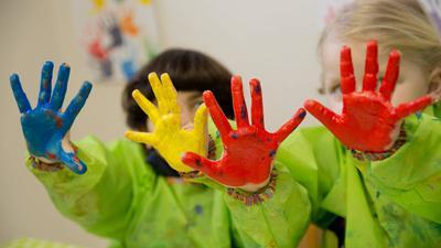 ARCHIV - Zwei Kinder spielen am 19.02.2015 mit Fingerfarben im Atelier eines Kindergarten in Würzburg (Bayern). Wegen nicht bezahlter Kindergartengebühren haben bayerische Kommunen Ausfälle in Millionenhöhe.