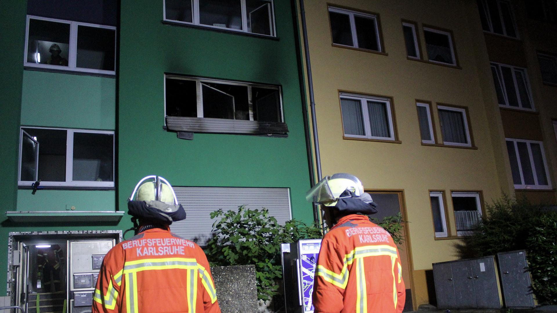 Zwei Feuerwehrleute in Uniform blicken auf ein grünes Mehrfamilienhaus. An einem Fenster im zweiten Stock erkennt man schwarze Rückstände eines Brandes.