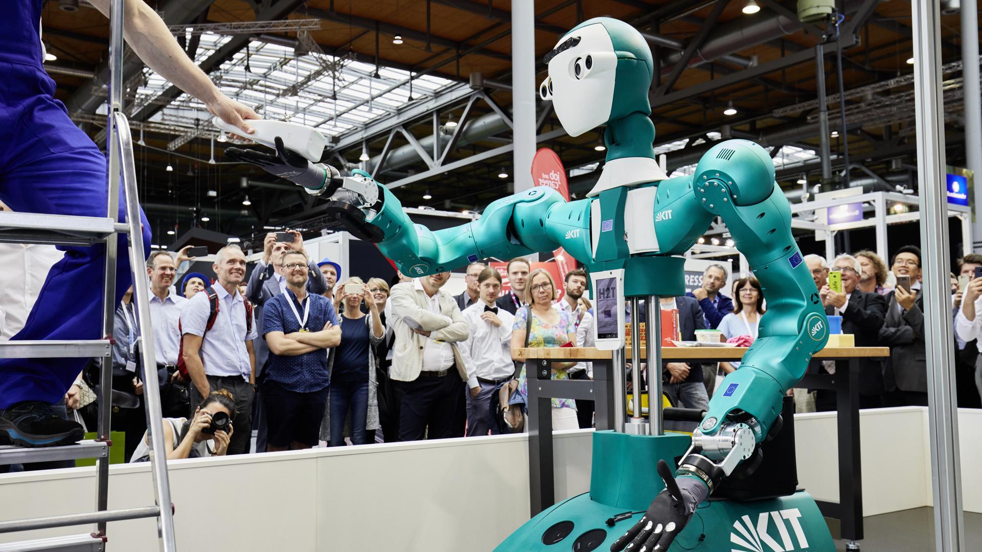 Mit seinem menschenähnlichen Körper kann der humanoide Assistenzroboter ARMAR-6 für den Menschen geschaffene Werkzeuge wie Bohrmaschinen oder Hammer verwenden. Seine künstliche Intelligenz erlaubt es ihm unter anderem, selbstständig Aufgaben im Kontext der Wartung industrieller Anlagen zu übernehmen.
