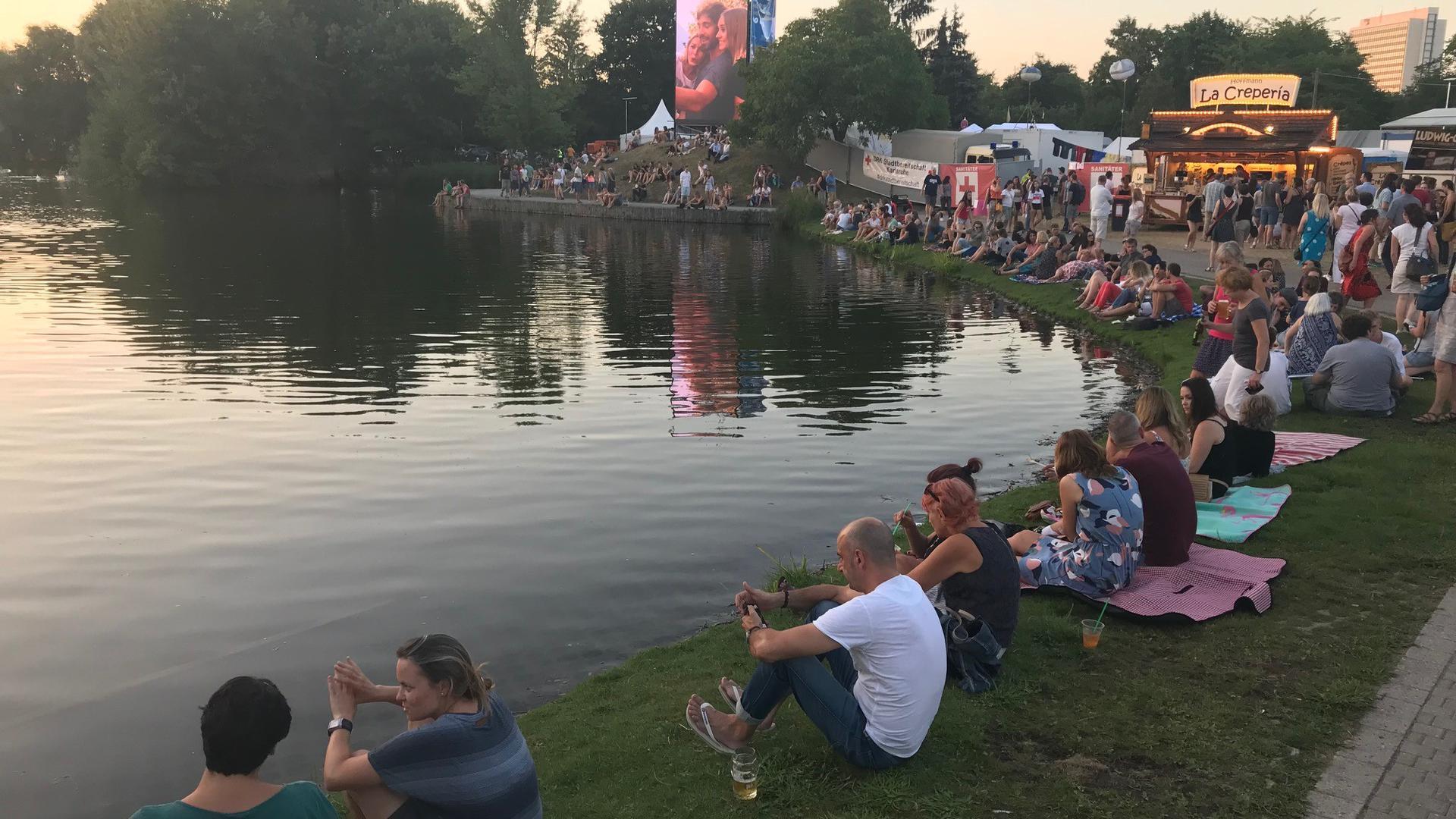 Viele Menschen sitzen am Ruderbootsee in der Günther-Klotz-Anlage und lassen bei einem Bier den Arbeitstag ausklingen.