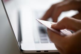 Laptop und eine Hand, die eine Kreditkarte hält