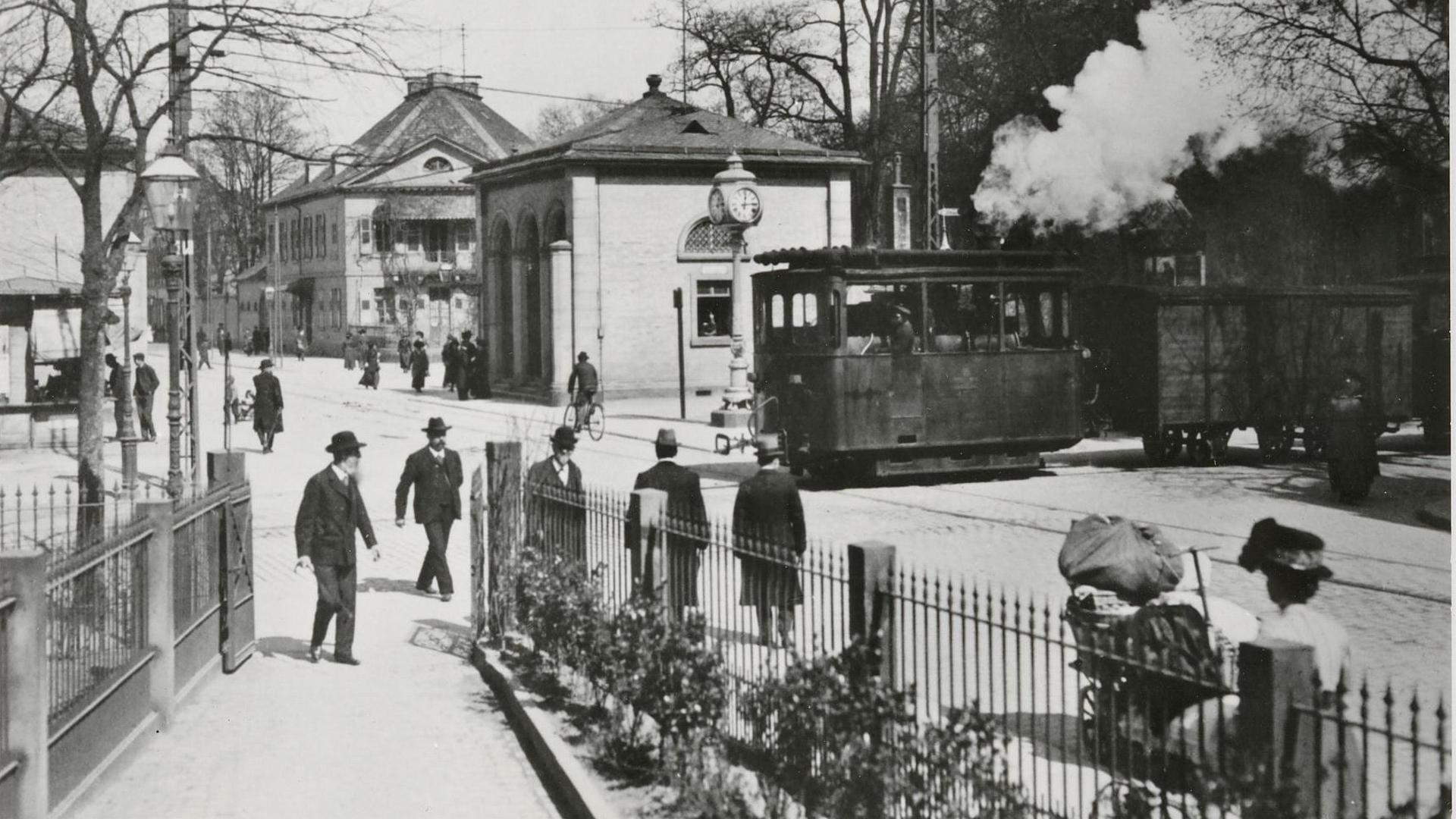 Das Lobberle: Die Karlsruher Lokalbahn zwischen Spöck und Durmersheim, rollt am Karlstor auf der Kriegsstraße quer über die Straßenbahngleise. Dampf steigt in dieser Szene um 1910 vor dem Palaispark – heute Standort des BGH – auf.