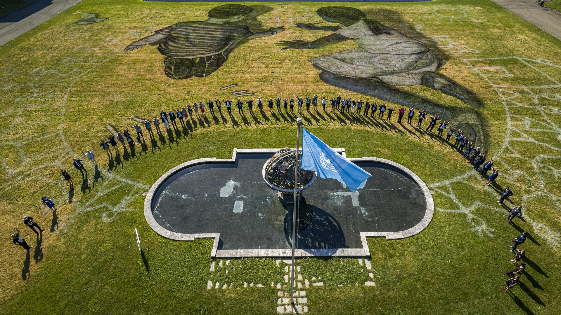 Das Land Art Gemälde «World in Progress» des französisch-schweizerischen Künstlers Saype wird auf der Wiese vor dem Hauptsitz der Vereinten Nationen enthüllt. Abgebildet sind zwei Kinder, die ein Bild aus Kreide malen. Das Kunstwerk wurde anlässlich des 75. Jahrestages der Unterzeichnung der Charta der Vereinten Nationen am 26.06.1945 mit biologisch abbaubaren Farben auf die Wiese gemalt. +++ dpa-Bildfunk +++