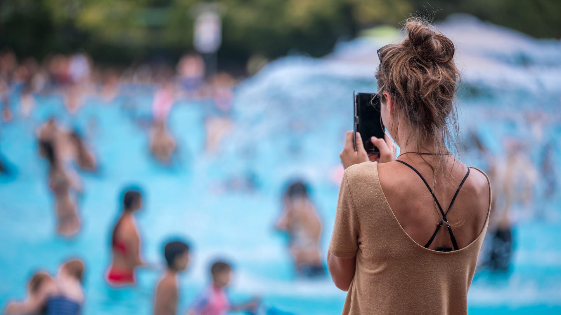 """ILLUSTRATION - Eine junge Frau fotografiert mit ihrem Handy im Prinzenbad. Hunderttausende Kinder und Erwachsene folgen minderjährigen Influencern auf Youtube, Instagram oder TikTok durch ihren Alltag, in den Park oder ins Schwimmbad. Hinter der Kamera, den Accounts und den Verträgen mit Unternehmen, die in den Videos ihre Produkte platzieren, stehen oft die Eltern. Es ist ein Phänomen in sozialen Netzwerken und auf Internetkanälen, das dem Deutschen Kinderhilfswerk langsam ein wenig unheimlich wird. (zu dpa: """"Kinderhilfswerk fordert besseren Schutz von Kinder-Influencern"""") +++ dpa-Bildfunk +++"""