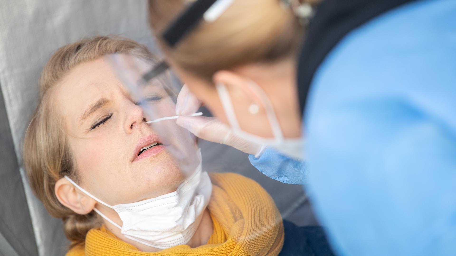 Eine Frau lässt sich während der Vorstellung von Corona-Schnelltest-Zentren der Drogeriemarktkette dm mit einem Antigentest von einer medizinischen Fachangestellten testen.