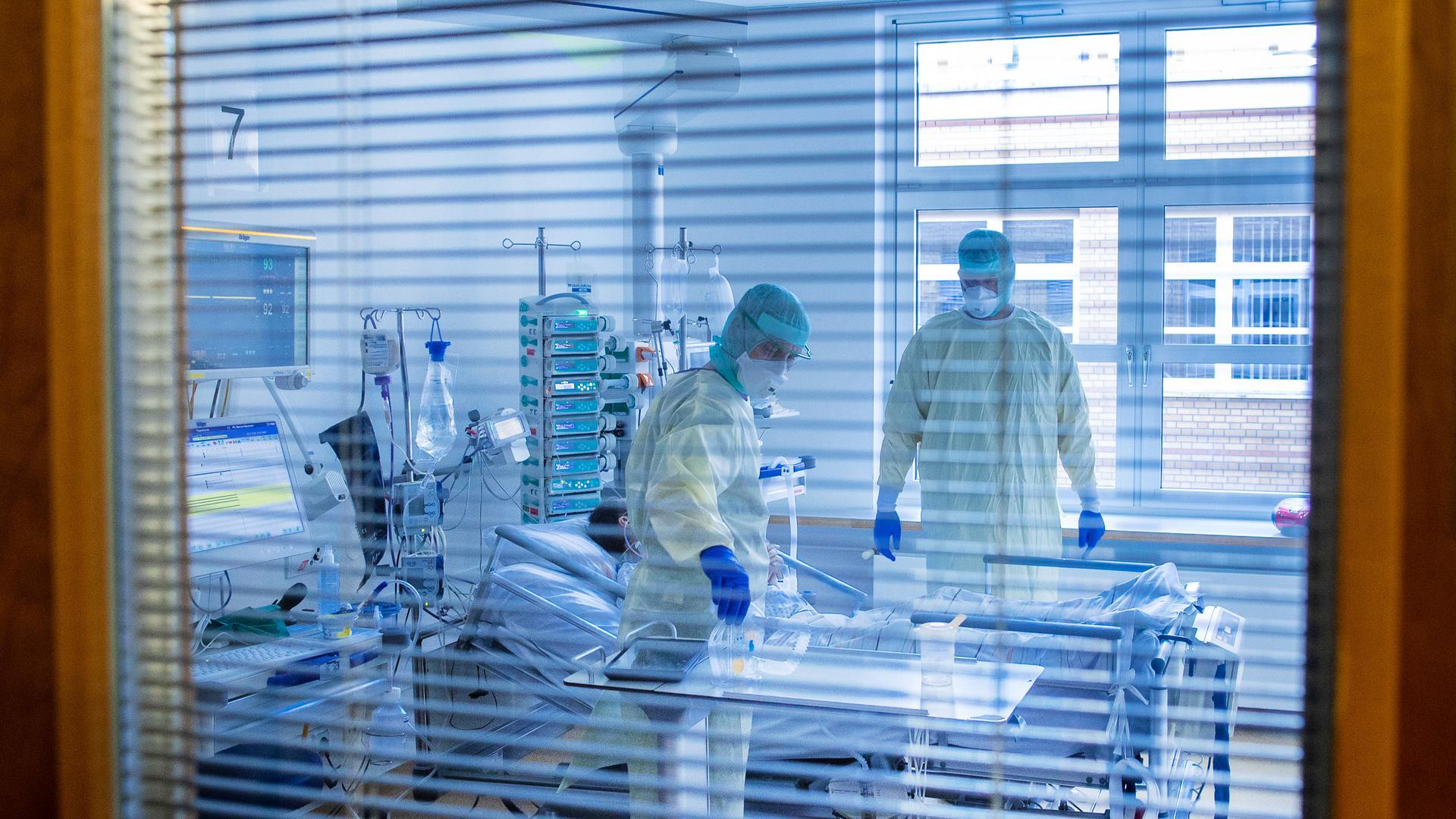 """Mediziner und Pfleger versorgen einen an Covid-19 erkrankten Patienten in einem Zimmer des besonders geschützten Teils der Intensivstation des Universitätsklinikums Greifswald. (zu dpa """"Engpass bei Intensivbetten droht - Verlegung von Patienten"""") +++ dpa-Bildfunk +++"""