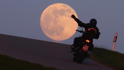 """Ein Motorradfahrer fährt vor dem aufgehenden Vollmond über eine Hügelkuppe. Am 27. April 2021 kommt es zu einem sogenannten """"Supermond"""". Dann ist die Entfernung zwischen Mond und Erde geringer als sonst. +++ dpa-Bildfunk +++"""