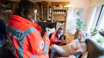 """Die Notfallsanitäter Miriam Görg und Jürgen Becker vom Deutschen Roten Kreuz (DRK) versorgen eine Seniorin, die in ihrem Wohnzimmer einen Schlaganfall erlitten hatte. Der Sohn und ein Bekannter der Familie verfolgen den Einsatz. Aufgrund der Corona-Einschränkungen dürfen Sie die Patientin nicht ins Krankenhaus begleiten. Im Jahr 2021 feiert das Deutsche Rote Kreuz (DRK) 100-jähriges Jubiläum. (Zu dpa Reportage """"100 Jahre DRK - Vom Miteinander geprägt"""" vom 07.05.2021"""") +++ dpa-Bildfunk +++"""