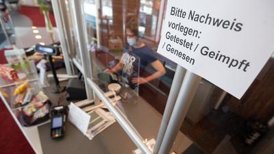 """Ein Schild """"Bitte Nachweis vorlegen: Getestet, Geimpft, Genesen"""" hängt an der Kasse vom Kino am Raschplatz."""