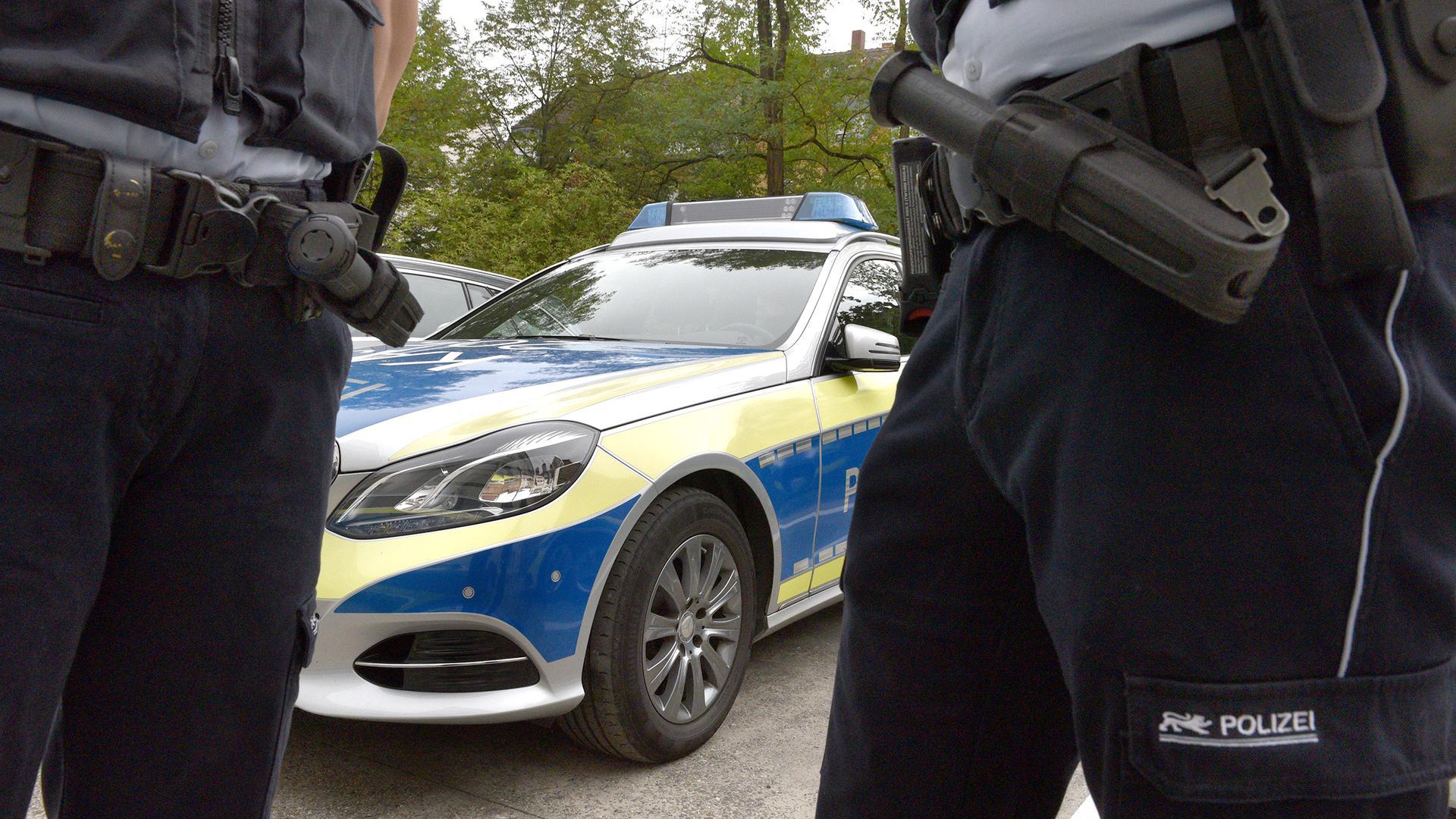 Zwei Polizisten stehen auf einem Parkplatz vor einem Polizeiauto. (Symbolbild)