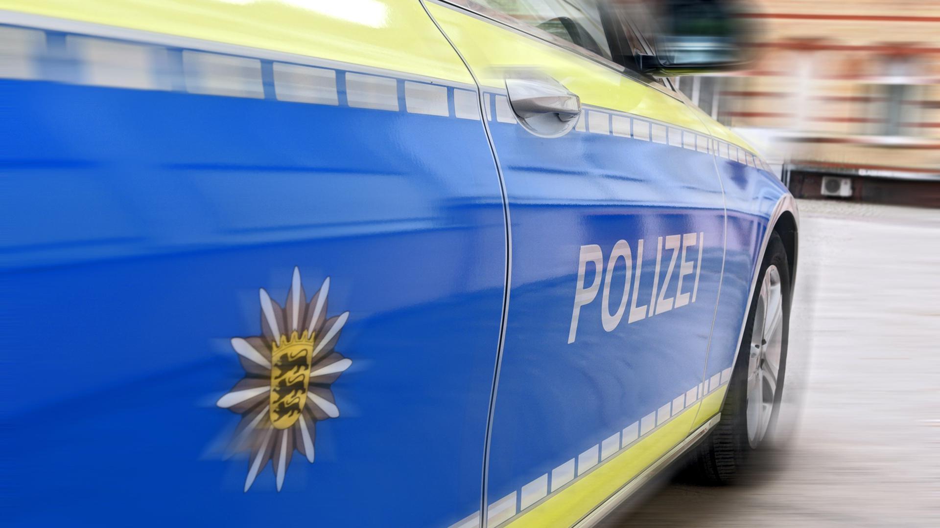 Ein Polizeiauto fährt auf einem Parkplatz. (Symbolbild)