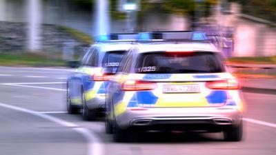 Zwei Polizeiautos fahren auf der Straße. (Symbolbild)