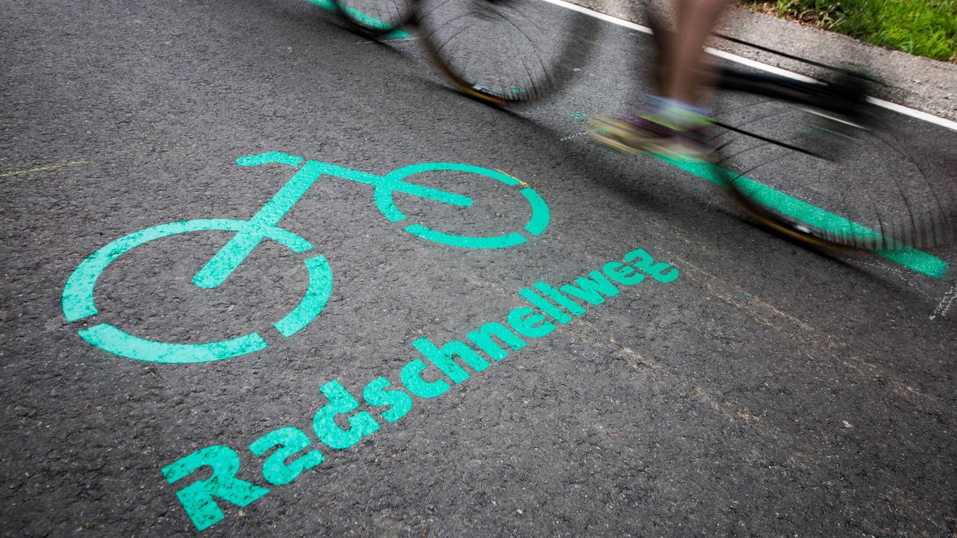 31.05.2019, Baden-Württemberg, Böblingen: Radfahrer fahren nach der Eröffnung des Radschnellwegs zwischen Böblingen/Sindelfingen und Stuttgart an einer Aufschrift auf dem Asphalt vorbei. Der erste Radschnellweg in Baden-Württemberg ist am 31.05.2019 für den Verkehr freigegeben worden. Foto: Christoph Schmidt/dpa +++ dpa-Bildfunk +++   Verwendung weltweit