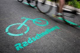 31.05.2019, Baden-Württemberg, Böblingen: Radfahrer fahren nach der Eröffnung des Radschnellwegs zwischen Böblingen/Sindelfingen und Stuttgart an einer Aufschrift auf dem Asphalt vorbei. Der erste Radschnellweg in Baden-Württemberg ist am 31.05.2019 für den Verkehr freigegeben worden. Foto: Christoph Schmidt/dpa +++ dpa-Bildfunk +++ | Verwendung weltweit