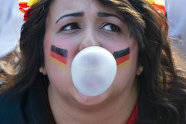 Beruhigt die Nerven: Eine Frau pustet während eines Fußballspiels der deutschen Mannschaft eine Kaugummi-Blase.