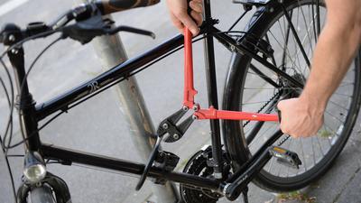 Ein Mann versucht mit einem Bolzenschneider ein Fahrradschloss aufzubrechen.
