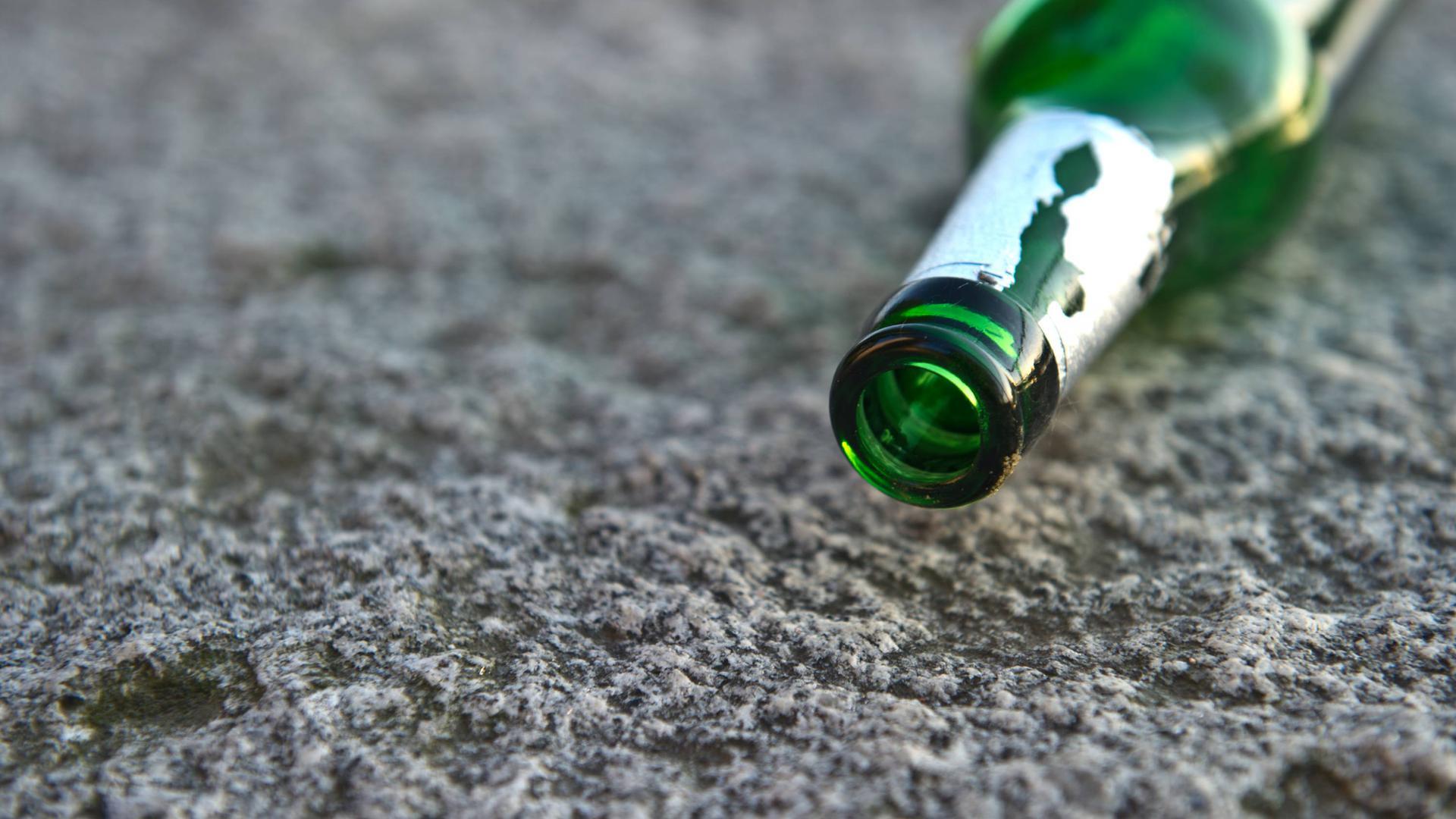 Eine Bierflasche liegt auf einer Steinbank.