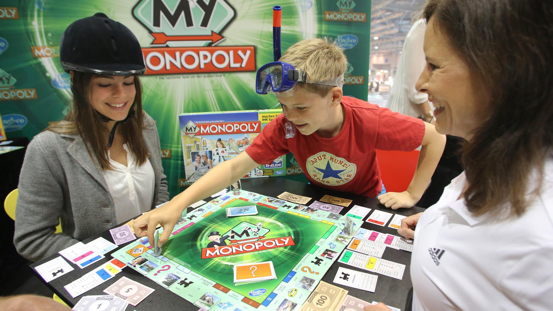 """Das personalisierte Brettspiel """"Monopoly"""" (Hasbro) wird auf der Messe """"Spiel'14"""" in Essen (Nordrhein-Westfalen) von einer Familie getestet."""