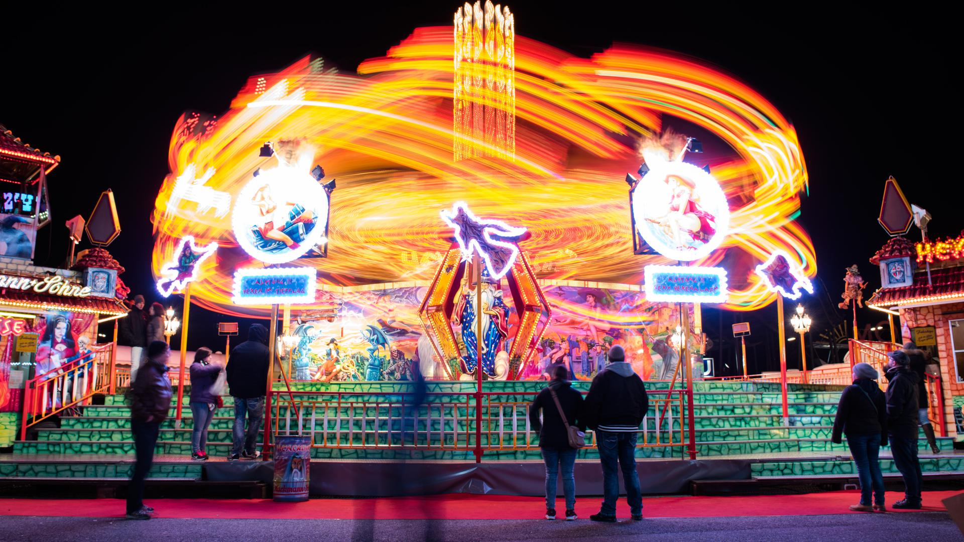 """Das Fahrgeschäft """"Hexentanz"""" zieht am 20.03.2016 in Hamburg auf dem Volksfest """"Hamburger Dom"""" bunte Lichtstreifen (Aufnahme mit langer Belichtungszeit). Zum vergangenen Wochenende hat der Frühlingsdom eröffnet. Foto: Daniel Bockwoldt/dpa ++ +++ dpa-Bildfunk +++"""