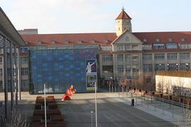 Außenansicht des Zentrums für Kunst und Medien (ZKM) in Karlsruhe mit seinem blauen Glaswürfel-Anbau und der roten Kunstskulptur auf dem Vorplatz.