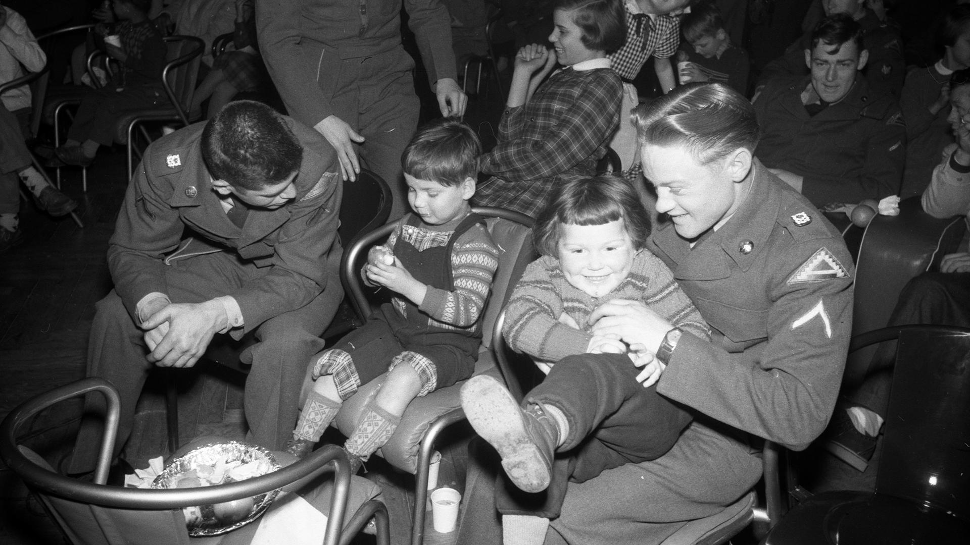 Essen und spielen mit GIs: In der Nachkriegszeit luden die US-Streitkräfte in Karlsruhe regelmäßig bedürftige Kinder zu großen Feiern ein.  Dieses Bild zeigt das Erntedankfest 1956 mit Kindern aus dem Sybelheim.