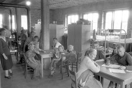 Durchgangslager für Sowjetzonenflüchtlinge in der Appenmühle. Blick in einen Gemeinschaftssaal. Tische, im Hintergrund doppelstöckige Betten und Schränke.