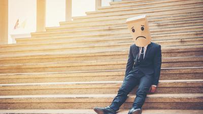 Unser Bild zeigt einen Mann auf Treppenstufen, der eine Tüte mit aufgemaltem, traurigen Gesicht über dem Kopf trägt, um nicht erkannt zu werden.