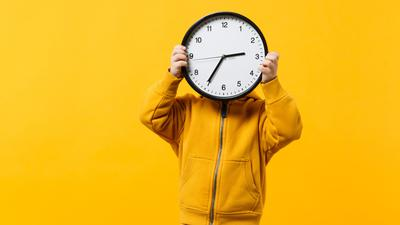 Little kid boy 3-4 years old wearing yellow clothes hold clock isolated on orange wall background, children studio portrait. People sincere emotions, childhood lifestyle concept. Mock up copy space