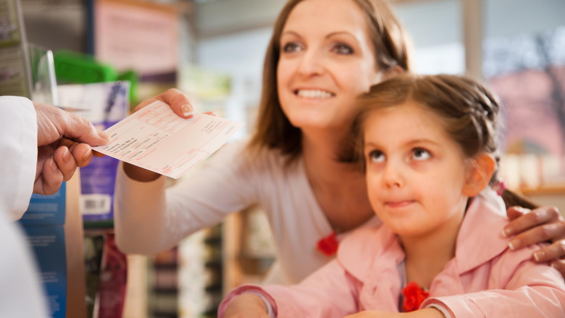 Mutter mit Kind holt in der Apotheke ein Medikament ab.