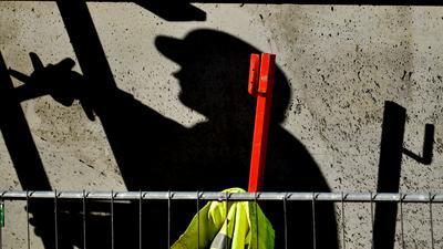 Ein Arbeiter ist auf einer Baustelle beschäftigt und wirft dabei einen dunklen Schatten.