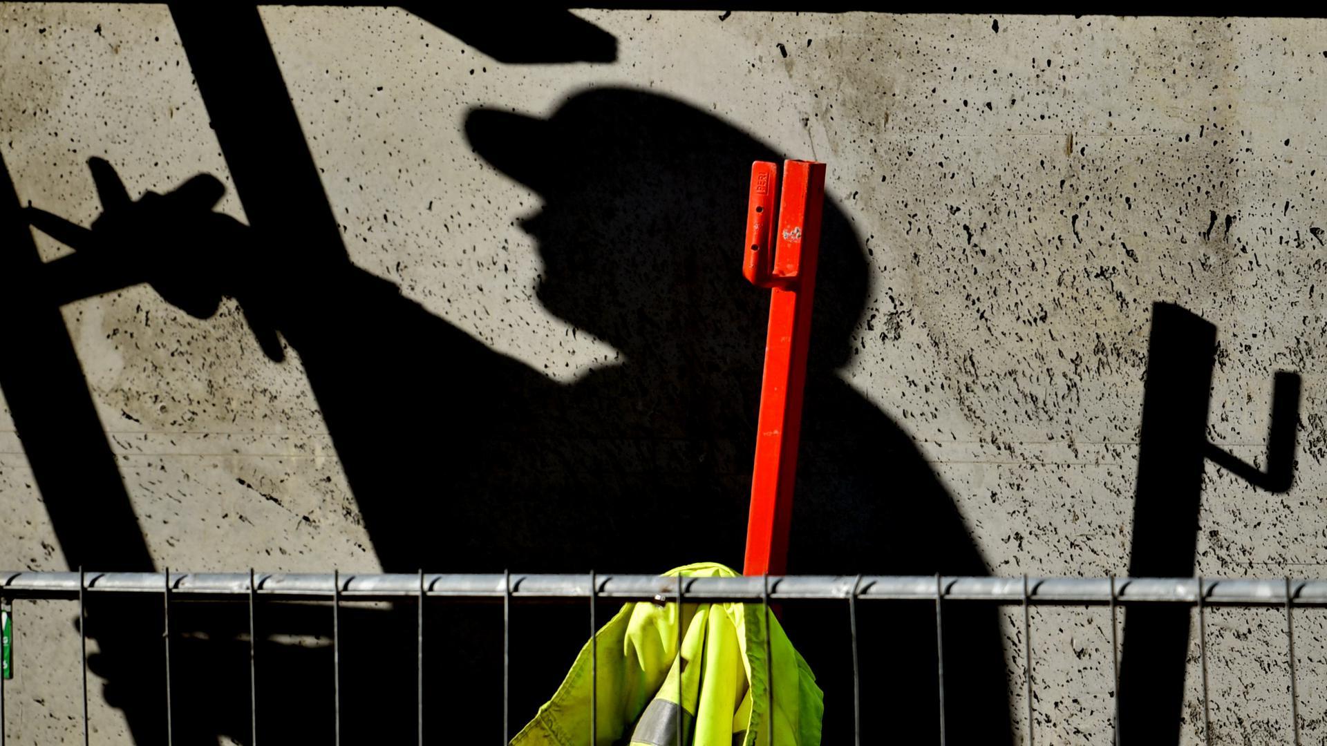 ARCHIV - 05.02.2015, Brandenburg, Potsdam: Illustration - Ein Arbeiter ist auf einer Baustelle beschäftigt und wirft dabei einen dunklen Schatten. (zu dpa «Gewerkschaft:Auf dem Bau sinkt die «Corona-Disziplin»») Foto: Ralf Hirschberger/dpa-Zentralbild/dpa +++ dpa-Bildfunk +++