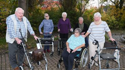 Sechs Heimbewohner sind miteinander im Garten. Fünf stützen sich auf Rollatoren, eine Dame sitzt im Rollstuhl.