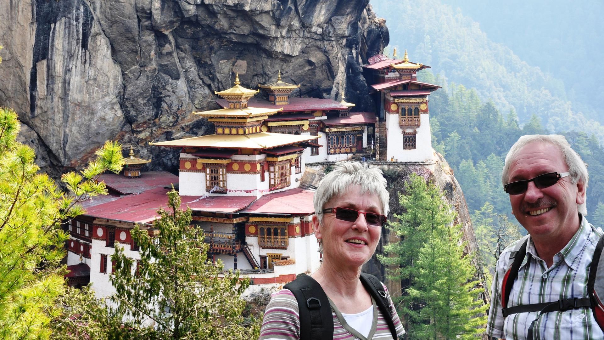 """Zu hohen Himalaya-Bergen: das Ehepaar Seyfried vor dem Tigernest-Kloster im """"Land des Glücks"""" Bhutan."""