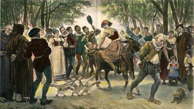 Eine Frau wird rücklings auf einem Esel sitzend durch die Straßen geführt.