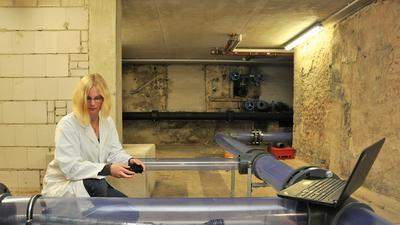 Eine Wissenschaftlerin steuert ein Gerät zur Inspektion von Wasserleitungen in einer Versuchsanlage in Dresden.