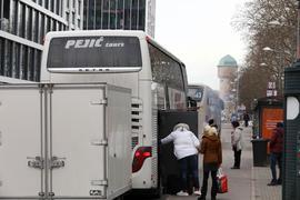 Menschen steigen am Karlsruher Hauptbahnhof in einen Reisebus.