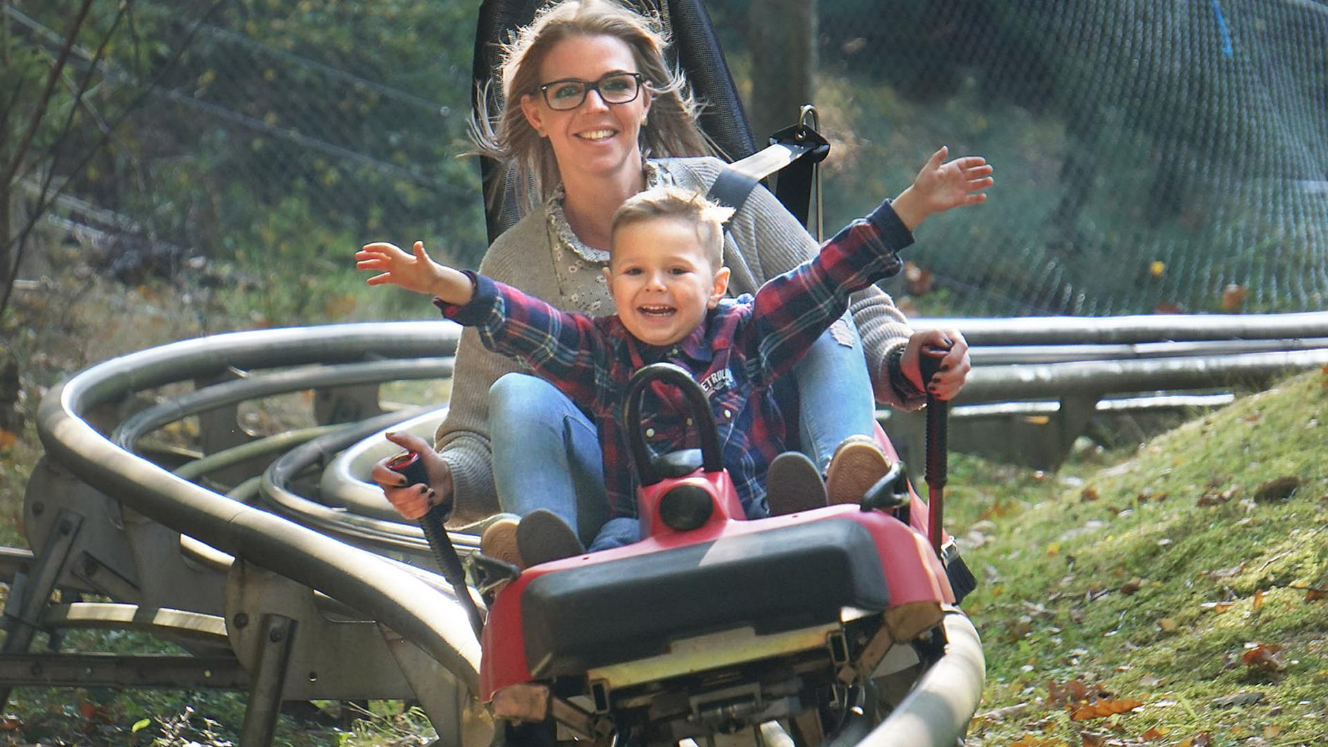 Mutter und Kinder in der Sommerrodelbahn im Kurpfalz-Park im Pfälzer Wachenheim.