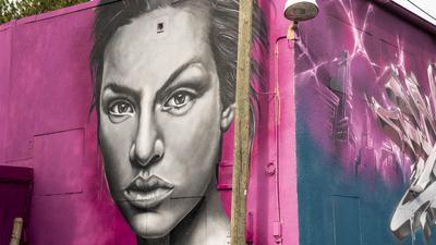 Ein Graffiti mit einem Frauenkopf an einer Wand
