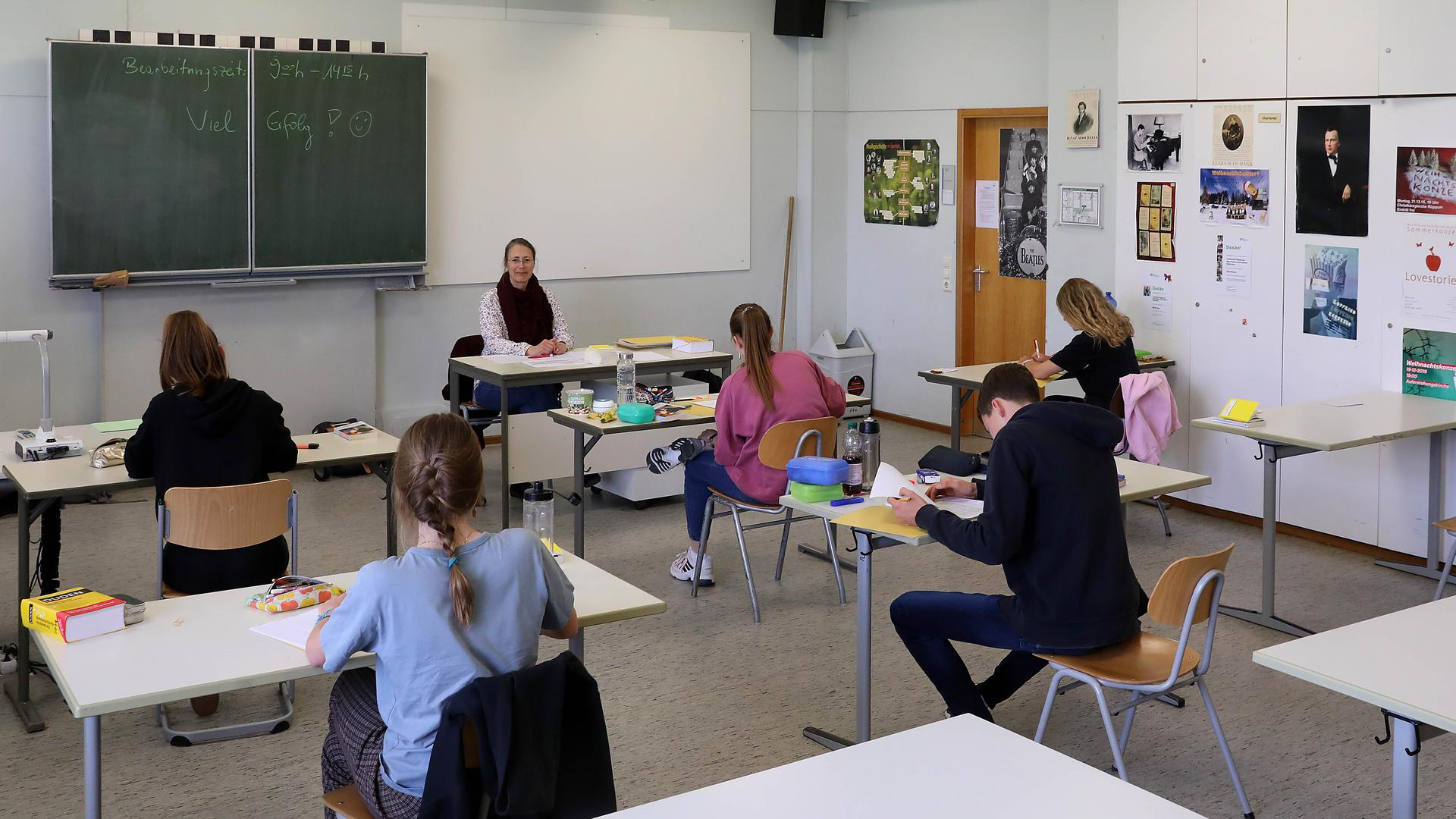Schüler sitzen mit Abstand in einer Klasse, vorne sitzt die Lehrerin am Tisch.