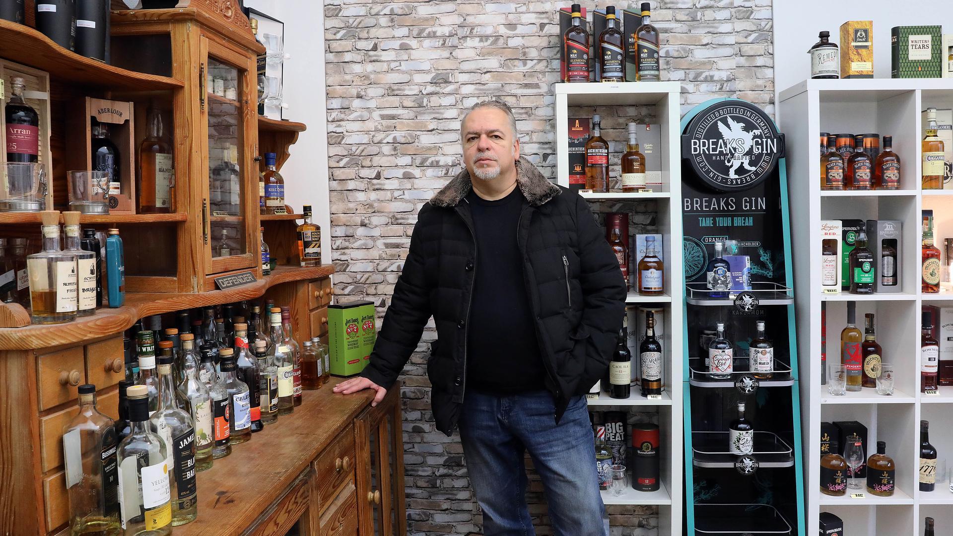 Mann steht vor Regal mit Wiskey-Flaschen