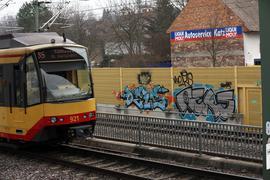 Straßenbahn neben Lärmschutzwand mit Graffiti