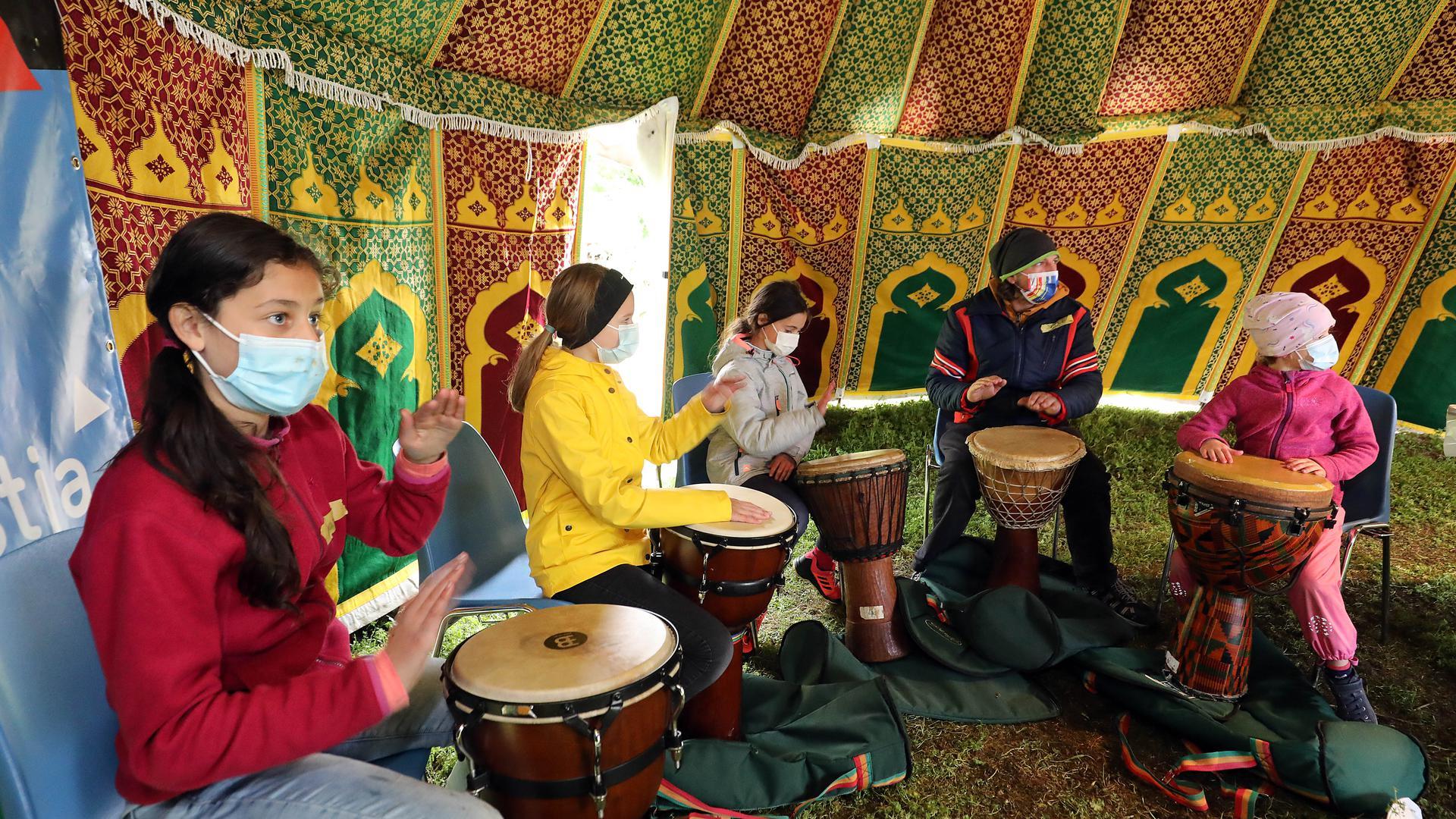 Sie haben den Rhythmus raus: Jochen Werner übt das Trommeln mit den Teilnehmerinnen des Kinderkulturfestival KiX im Otto-Dullenkopf-Park.