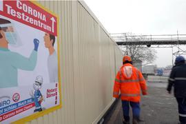 Arbeiter laufen bei der Raffinerie Miro in Karlsruhe an einem Schild vorbei, das auf ein Corona-Testzentrum hinweist.