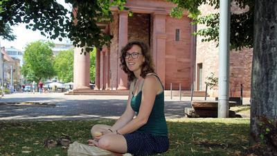 Eine Frau sitzt unter einem Baum im Gras. Vor ihr liegt ihr Mittagessen.