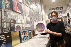 Der Besitzer des Plattenladens Discover in Karlsruhe hält eine Platte in der Hand.