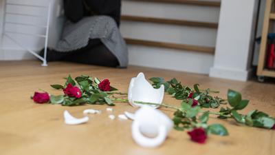 Auf dem Boden eines Wohnhauses liegen Scherben und verstreute Rosen.